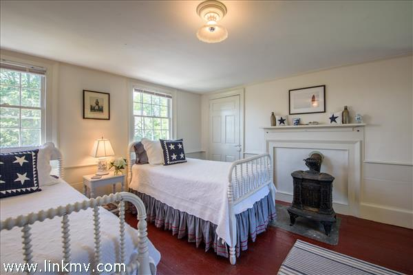 Wainscoting, wind pine boards, a coal stove add to the charm of this bedroom.