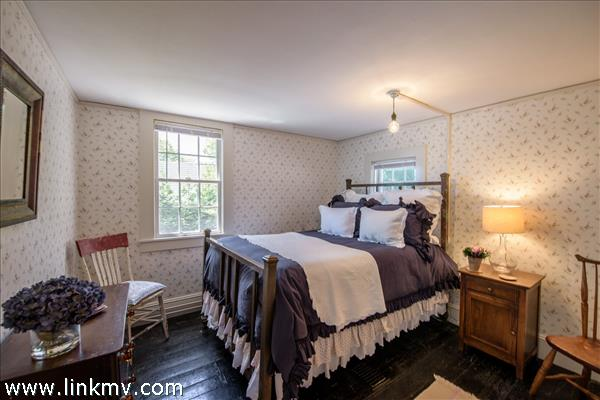 Tucked in the ell at the back of the house this delightful bedroom overlooks the stretch of lawn.
